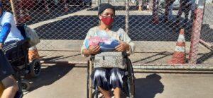 Imagem de uma mulher cadeirante segurando um cobertor que recebeu durante a campanha do Agasalho Solidário